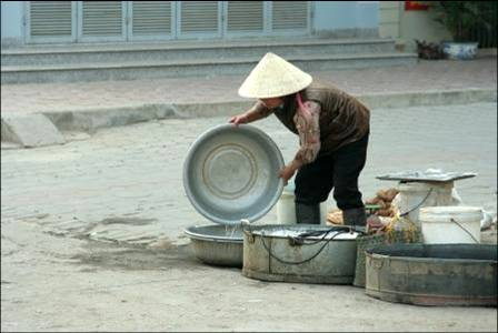 Woman washing dishes in Hanoi